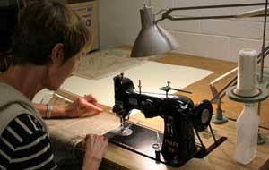 Volunteer sews protective sleeves