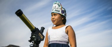 A student looks through a telescope.