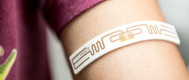 Low-powered wristband shown on a person's forearm.