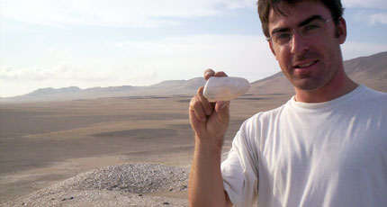 Matthieu Carré holds a 6,800-year-old mollusk collected from a site in Peru's Ica valley.