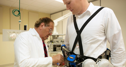 Dr. Victor Gura helps assistant John Kundzins don a demo version of the Wearable Artificial Kidney on Sept. 5, 2014.