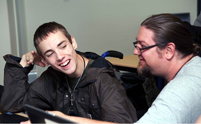 An educator assists a computing student