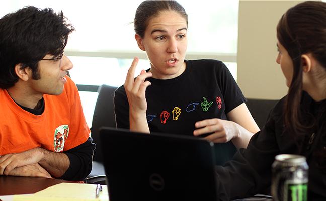 A TA interprets between a deaf computing student and a hearing TA.