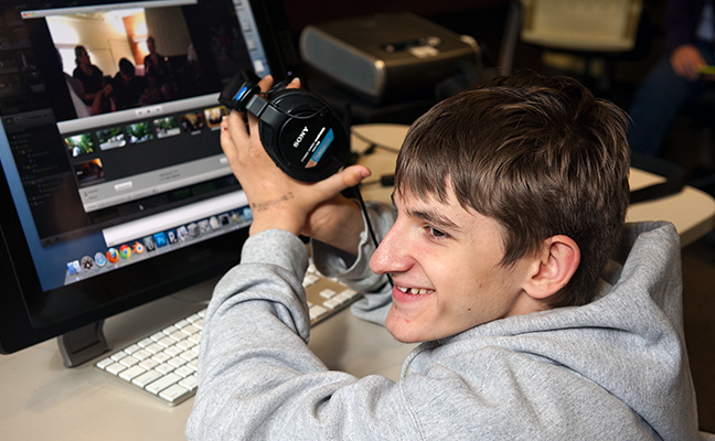A student uses headphones to work on a computing project