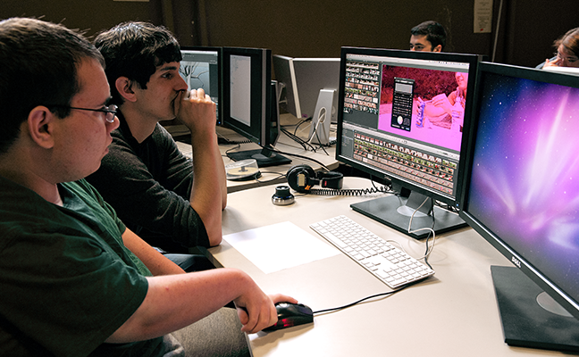 A student with a disability works with an educator to edit a video on a desktop computer