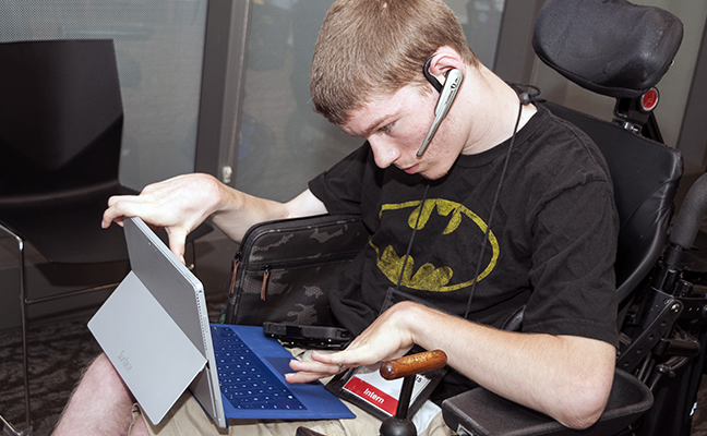 A student uses a headset, tablet, and keyboard to work on a project