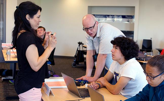 A student looks to an interpreter while the educator shows him how to design a website.