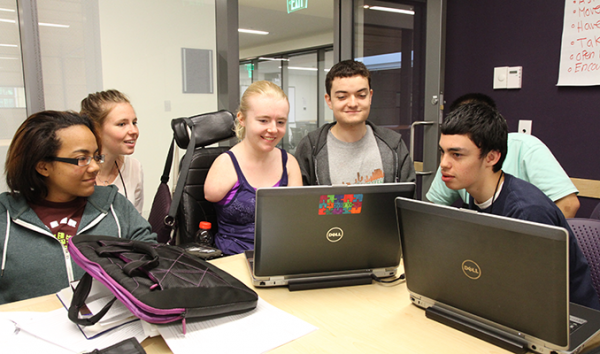 A diverse group of students working on a computer project