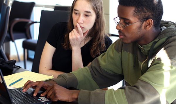 Two students collaborate on a computing project