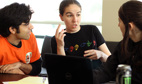 A sign language interpreter works with two computing students who have hearing impairments
