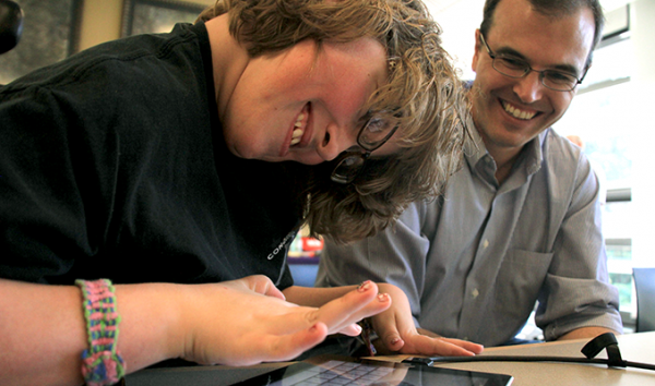 An instructor works with a student using a tablet