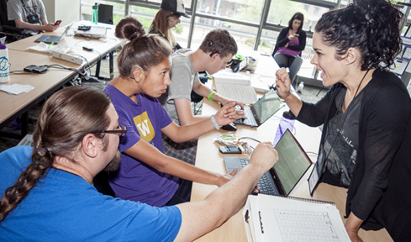 A computing student works with a sign language interpreter and a computing educator