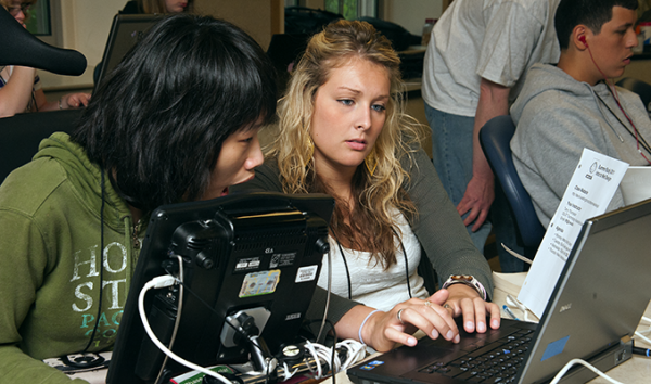 Two students use assistive technology to work on a computing project