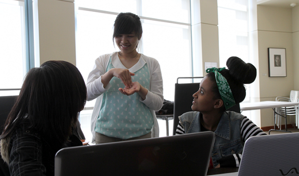 A computing student uses sign language to collaborate with others