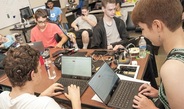 A group of students sit around a table coding on their laptops.
