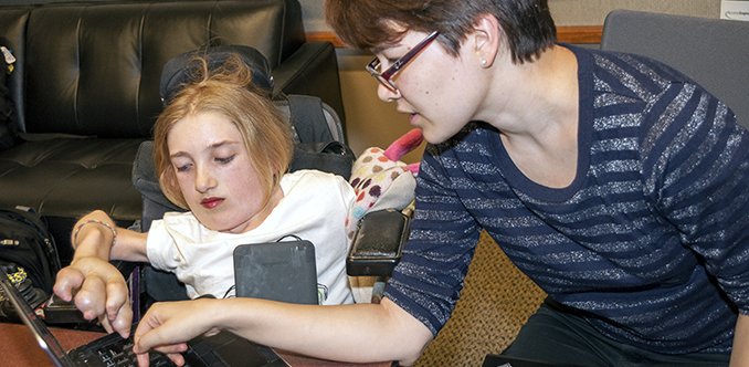 An instructor works with a student on a computing project