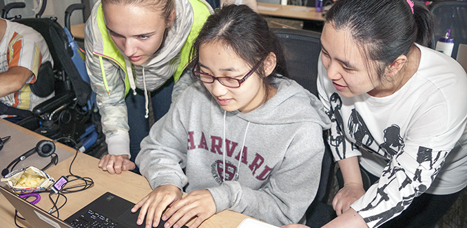 Three students work on a computing project together