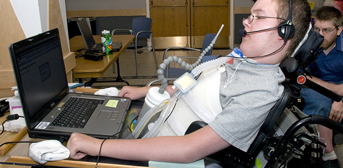 A student with a mobility impairment works on a computing project