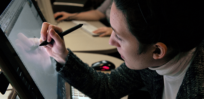 A student uses a stylus to work on a computing project