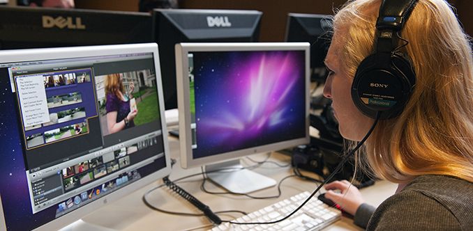 A student using headphones works on video editing on her computer