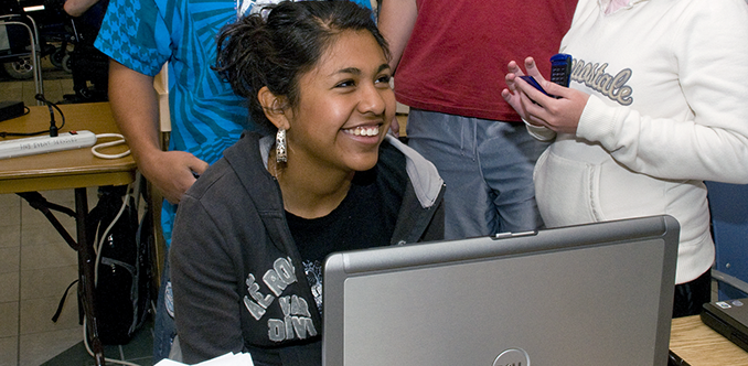 A group of students congregate around a computer