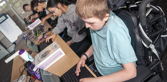 A group of students with diverse abilities work in a computer lab