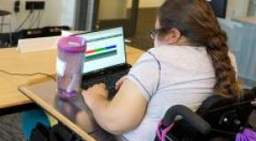 A student with a disability works on her computer.
