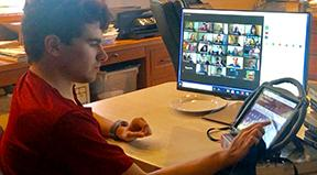 A student uses his Augmentative and Alternative Communication device to access a Zoom class.