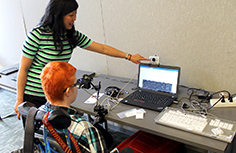 An instructor shows a student how to use assistive technology.