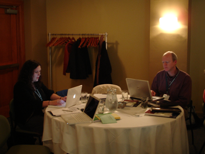 Two people working on laptops at a conference