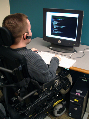 A student sitting in a wheelchair uses a computer