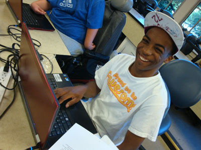 A student using a laptop smiles