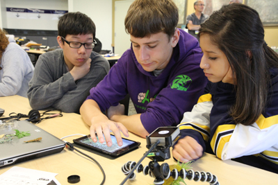 Three students working together on a tablet.