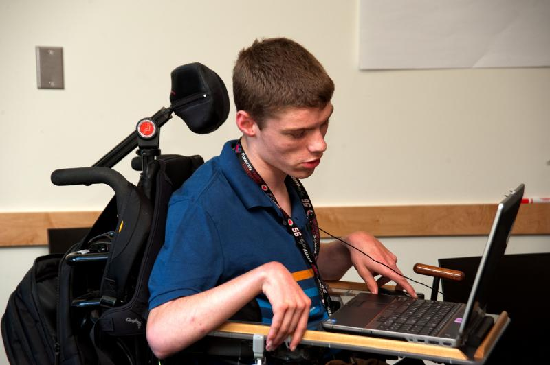 Image of student who uses a wheelchair, using a laptop.
