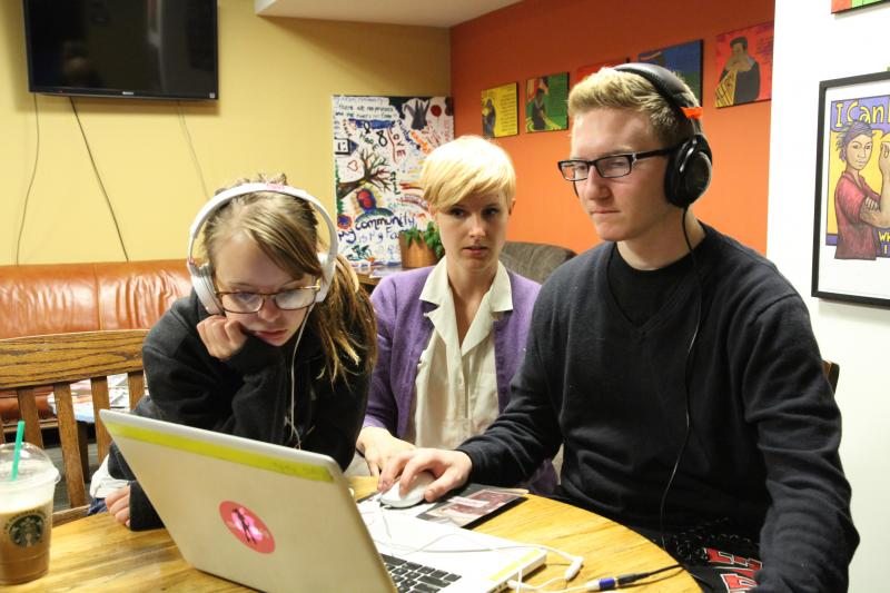 Two students view a computer with a mentor.