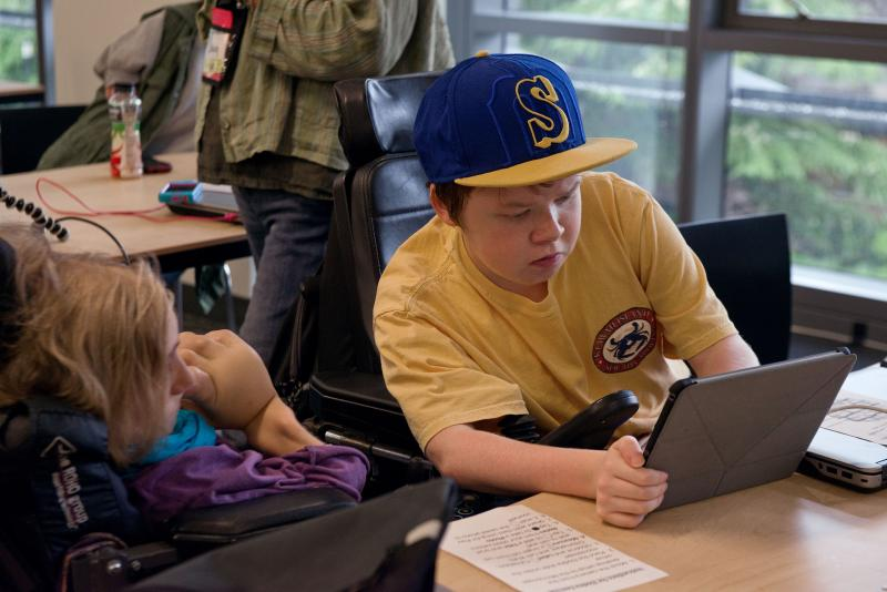 One student holds a tablet while another student looks on.