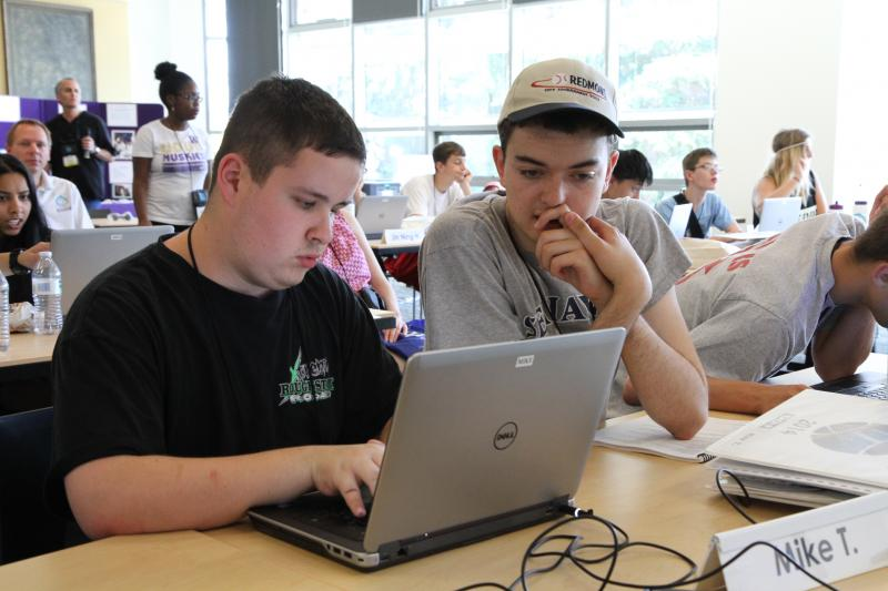 Two male students work together on a computer.