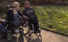 Two students in wheelchairs go down a college path.
