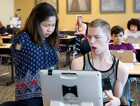 One DO-IT Scholar helps another Scholar complete a project on the computer during Summer Study 2016.