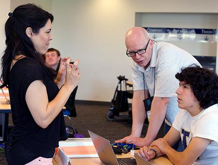 An interpreter signs while an instructor shows a students how to design a website.