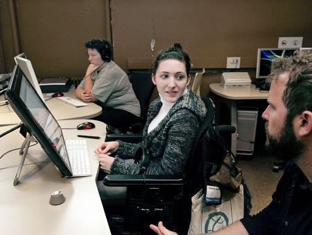 Image of a student working with an instructor in a computer lab.