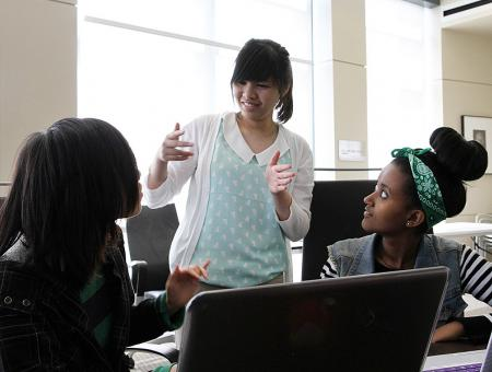 Group image of students collaborating with sign language during a computer lab.