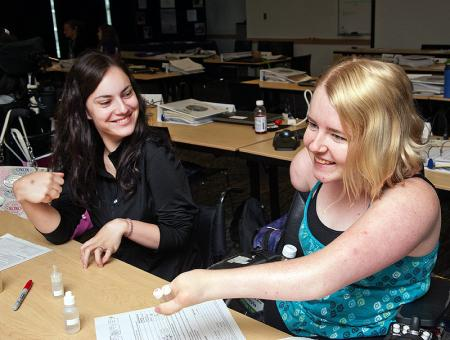 Image of two students laughing during a classroom project.