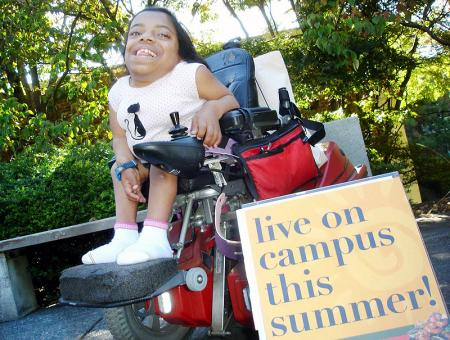 Image of a student in a wheelchair holding a sign.