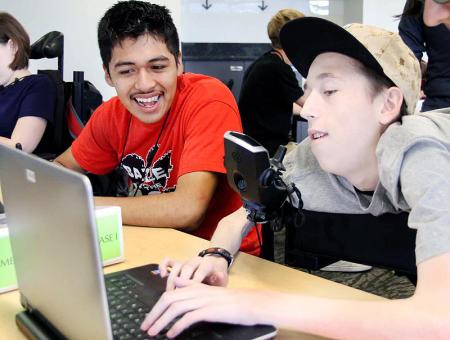 Image of two students working together on a laptop.