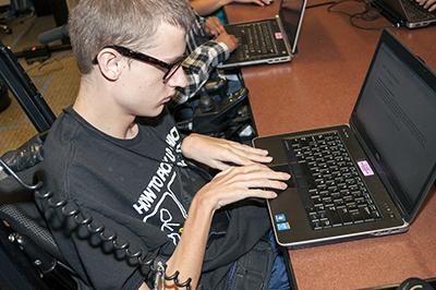 A boy in a wheelchair types on a computer.