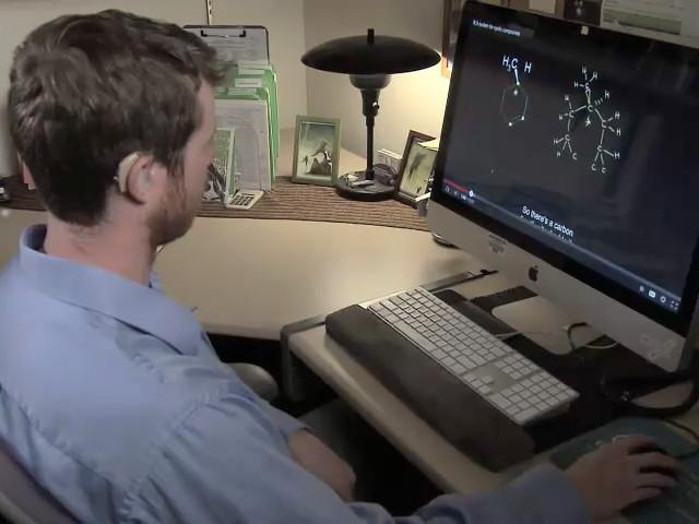 Still image from video: A deaf student watches a video with captions