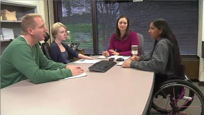 Still image from video: A diverse group of individuals meets around a large table
