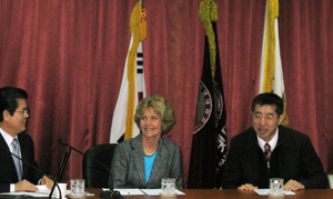 Picture of Drs. Burgstahler and Iwabuchi at a table in front of several flags.