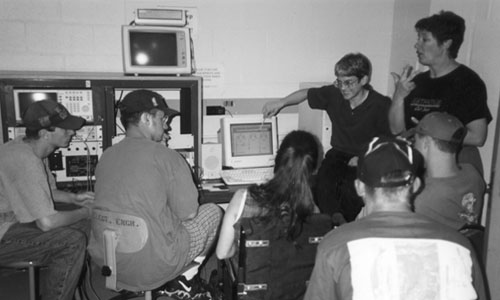 Picture of students working  together at a computer and a sign language interpreter is interpreting.